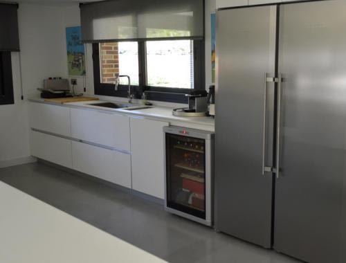 Cocina amplia que comunica con el exterior de la vivienda a través de una ventana corredera.