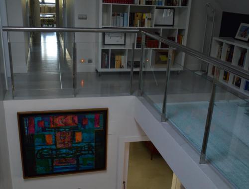Escalera principal y primera planta de una propiedad dónde el suelo se ha reformado bajo la técnica del microcemento.