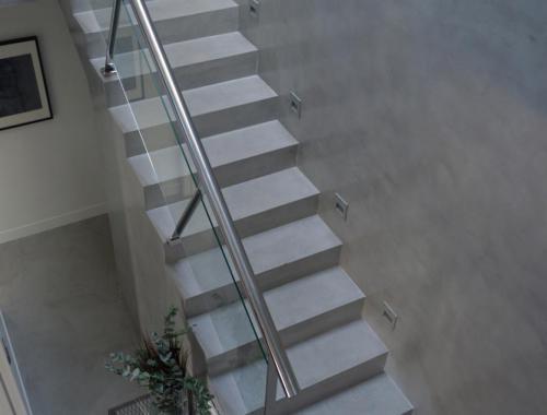 Escalera principal de una vivienda realizada bajo la novedosa técnica de microcemento.