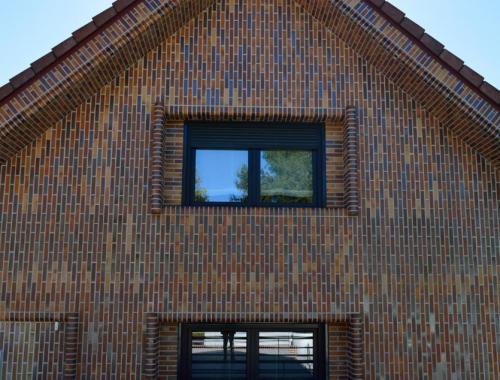 Fachada lateral de una casa con ventanas de PVC en color negro.
