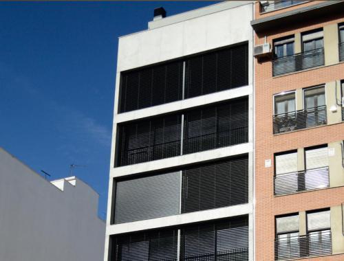 Fachada del edificio Ferrocarril 4BIS del arquitecto Israel Alba acristalada bajo unas correderas de aluminio.