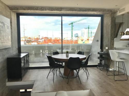 Balconera de dos hojas en aluminio negro mate situada en el salón de este ático del centro de Madrid.