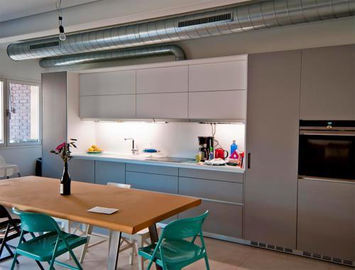 Cocina en tonos grisáceos con un toque de color que integra un excelente diseño y la utilidad del espacio para favorecer la comodidad de los clientes.