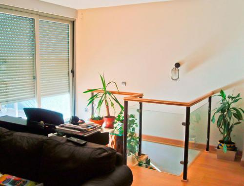 Ventana corredera de aluminio (izquierda) y barandilla (derecha) para el hueco de escalera en la planta superior de una vivienda.