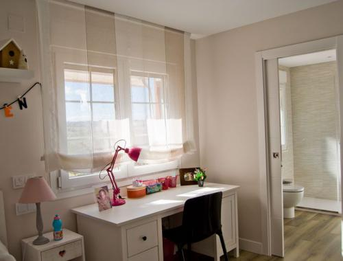 Ventana de PVC oscilobatiente con barrotillo en habitación infantil.