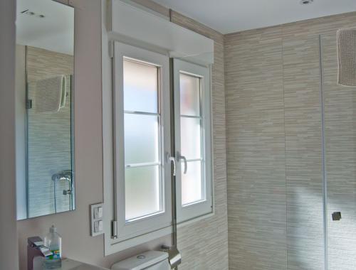 Ventana de PVC con cristal translúcido y persiana motorizada en baño.