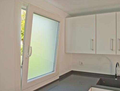 Ventana oscilobatiente de PVC con vidrio translúcido en cocina.