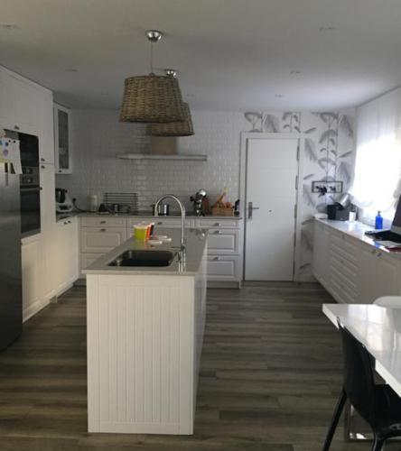 Cocina en tono blanco con isla central diseñada de forma personalizada según las exigencias del cliente.